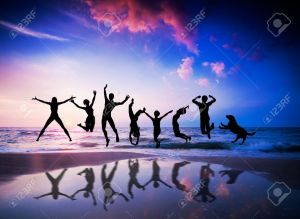 12504709-Happy-people-and-dog-jumping-together-on-the-sunset-beach-Stock-Photo